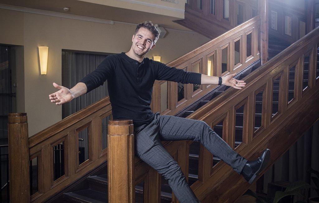 Perttu Pölönen istuu portaiden kaiteella kädet levällään..