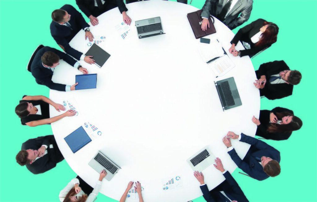 Ihmisiä pöydän ympärillä ylhäältä päin.